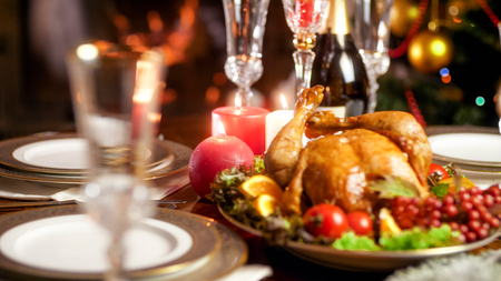 Closeup image of candles burning on served hristmas dinner table with baked chicken Stock Photo