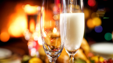 Closeup image of two champagne glasses being filled on Christmas family dinner