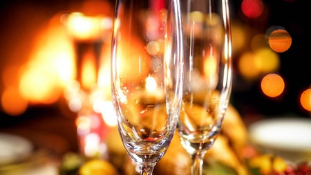 Closeup image of empty champagne glasses against burning fireplace and glowing Christmas tree