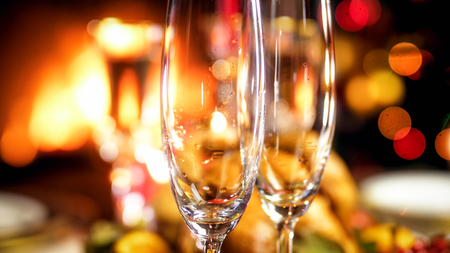 Closeup image of two empty champagne flutes against burning fireplace Stock Photo