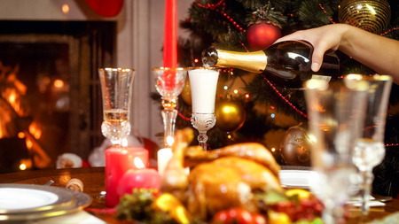 Closeup image of glasses being filled with champagne from bottle on family Christmas dinner