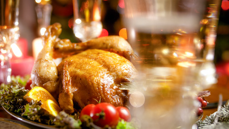 Closeup image of frshly baked chicken and champagne in glass on family festive dinner Stock Photo