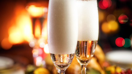 Closeup image of bubbles and foam in glasses of champagne against burning fireplace and Christmas tree