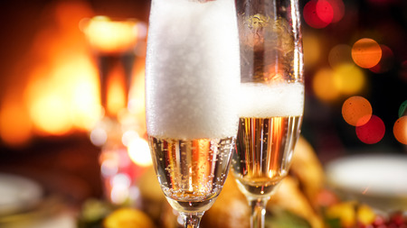 Closeup image of air bubbles and foam in two glasses of champagne