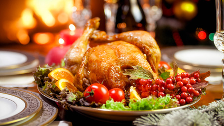 Closeup image of chicken baked with vegetable on family Christmas dinner nex tto fireplace Stock Photo