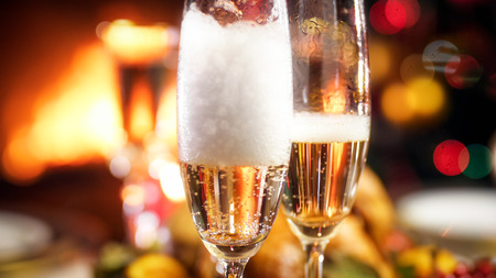 Closeup image of Champagne foam settling down in two glasses on Christamas dinner Stock Photo