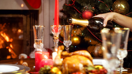 Closeup image of filling glasses with champagne on family dinner next to Christmas tree and burning fireplace