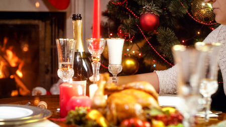 Closeup image of young woman taking bottle of champagne on Christmas family dinner Stock Photo