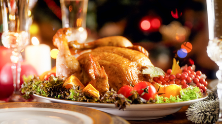 Closeup image of tasty baked chicken against glowing Christmas tree with colorful lights