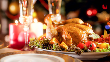 Closeup image of baked Christmas festive dining table with burning candles and baked chicken