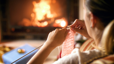 Closeup image of young woman sitting bu the fireplace and knitting woolen jumper