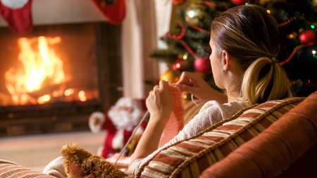 Young woman sitting by the fireplace and knitting scarf Stock Photo