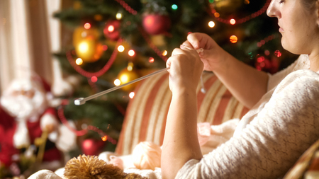 Portrait of beautiful young woman sitting in armchair next to CHristmas tree and knitting