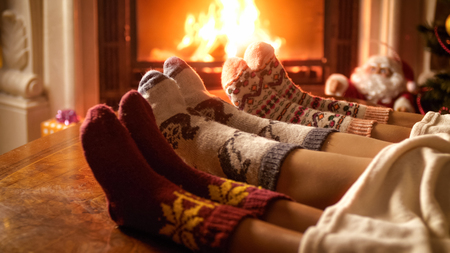 Toned photo of family feeling cosy by the fireplace at house