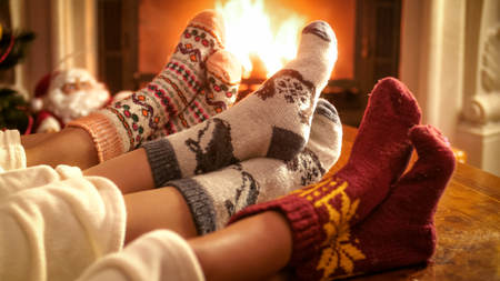 Family wearing knitted woolen socks warming feet at fireplace on Christmas eve Stock Photo