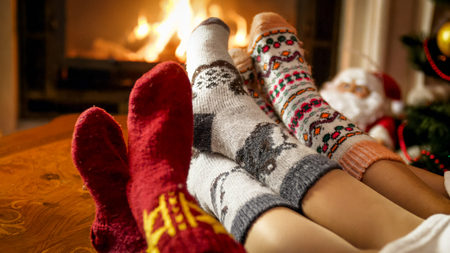 Closeup photo of female feet in warm woolen socks warming by the fireside at house Stock Photo
