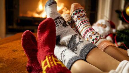 Closeup image of family lying at the fireplace in house and warming feet Archivio Fotografico