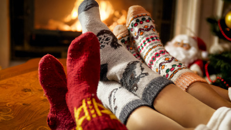 Young family in warm woolen socks warming by the fireside at house Archivio Fotografico