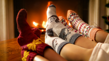 Toned image of family relaxing by the fireplace on Christmas eve Stock Photo