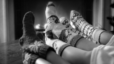Black and white image of family wearing knitted woolen socks relaxing by the fireplace