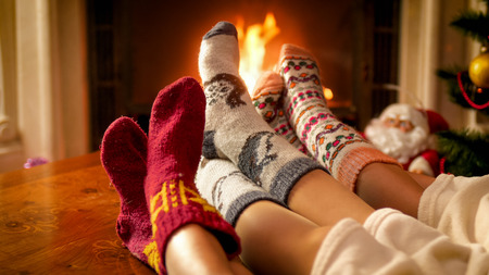 Closeup photo of parents qith child warming by the fireplace on cold winter day Stock Photo