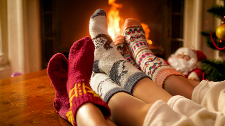 Closeup image of three persons in knitted woolen socks warming at the fireplace in chalet