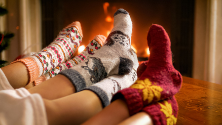 Closeup image of young family in knitted woolen socks lying under blanket and warming by the burning fire