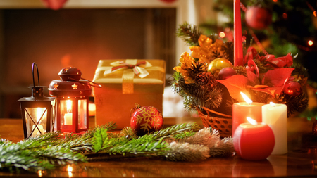 Closeup image of burning candles, gift box and Christmas wreath on wooden table Stock Photo
