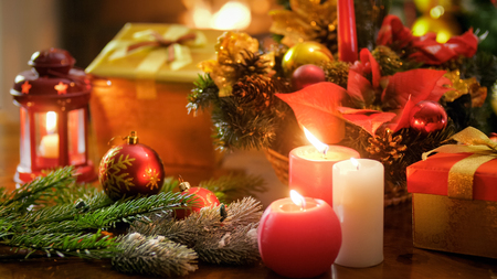 Closeup image of burning candles against Christmas decorations and gift boxes
