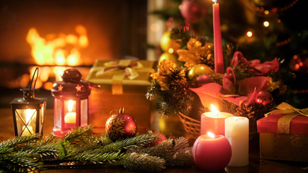 Closeup image of wooden table decorated for Christmas against burning fireplace at living room