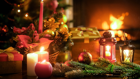 Closeup image of candles and lanterns against Christmas tree and burning fireplace Stock Photo