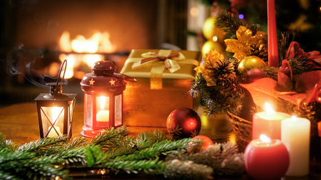Closeup image of golden gift box, candles and lanterns against Christmas tree and fireplace