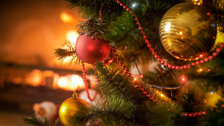 Closeup image of red and golden baubles on Christmas tree against burning fireplace