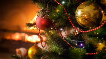 Closeup image of beautiful decorated Christmas tree branches with baubles, beads and lights