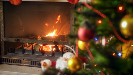 Burning fireplace in living room next to decorated Christmas tree Stock Photo