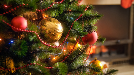 Closeup image of decorated Christmas tree branches against burning fireplace in living room at house Stock Photo