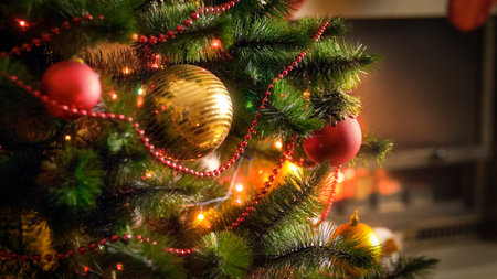 Closeup image of shiny baubles and glowing colorful light garlands on Christmas tree Stock Photo