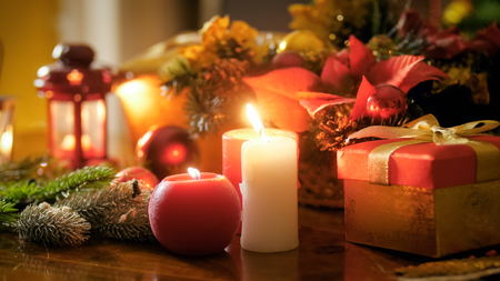 Closeup image of candles and lanterns on table decorated for Christmas