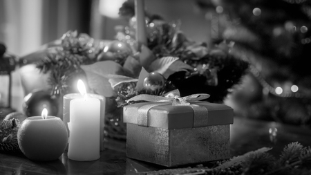 Black and white image of candles, gifts and baubles against Christmas tree