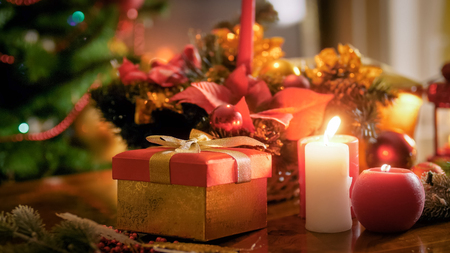Closeup image of gift box with golden ribbon and burning candles against Christmas tree at living room