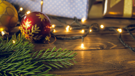CLoseup toned photo of red bauble, glowing light garlands and fir tree branch lying on wooden background