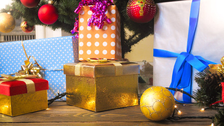 Closeup image of colorful baubles and gift boxes under Christmas tree at living room Stock Photo