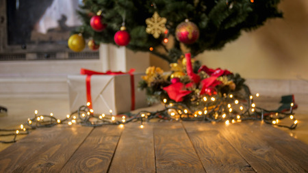 Perfect backgorund for Christmas and winter celebrations. Wooden table against decorated Christmas tree and glowing colorful lights