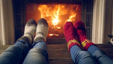 Getöntes Bild der romantischen Familie, die gestrickte Wollsocken trägt, die am Kamin wärmen