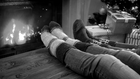 Black and white photo of family relaxing by the fireplace on Christmas eve