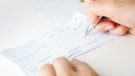 Closeup photo of businesswoman putting her signature on personal bank cheque with pen Stock Photo