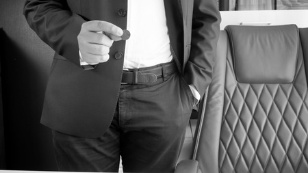 Black and white photo of businessman holding coin in hand