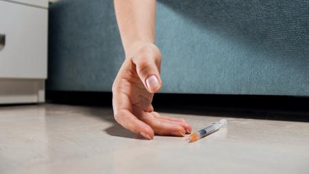 Closeup photo of empty syringe falling from female hand lying on floor. Drug addiction. Overdose of narcotics.