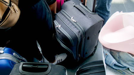 Closeup photo of people with suitcases waiting for flight in airport terminal
