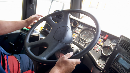 Closeup image of man holding hands on truck steering wheel